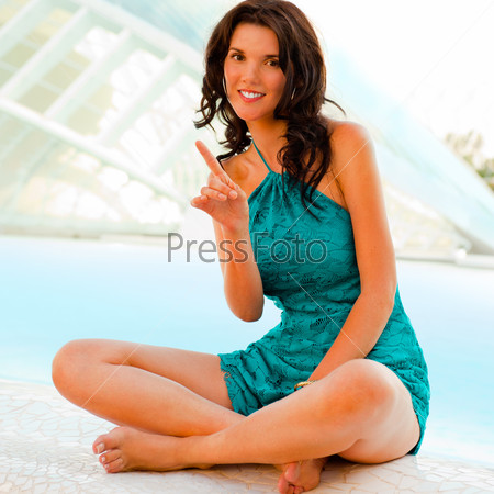 Young woman relaxing near pool at modern tropical resort with st