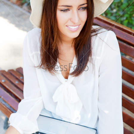 Young elegant woman wearing straw hat and white dress with lapto