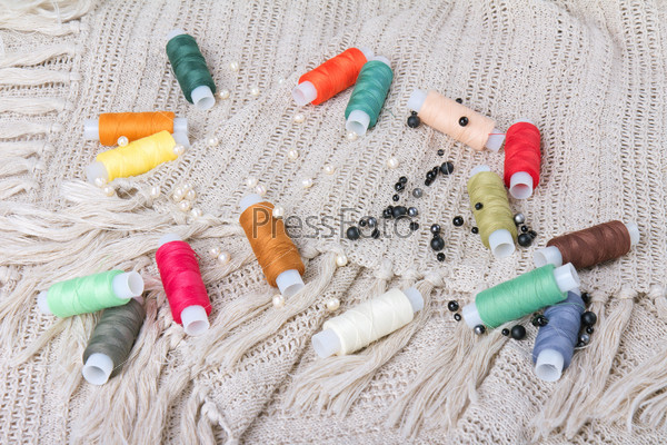 colorful threads and beads on a fabric background