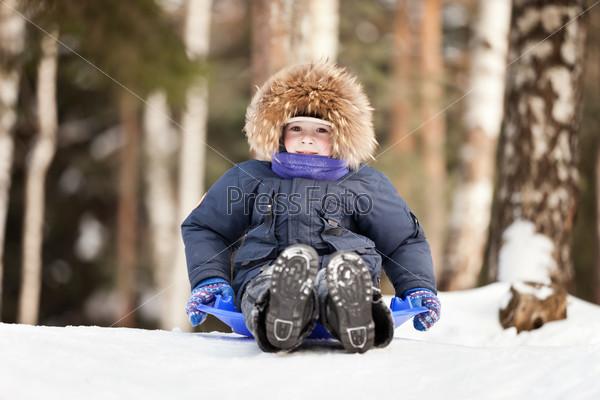 Маленький веселый мальчик катается с горки на ледянке зимой