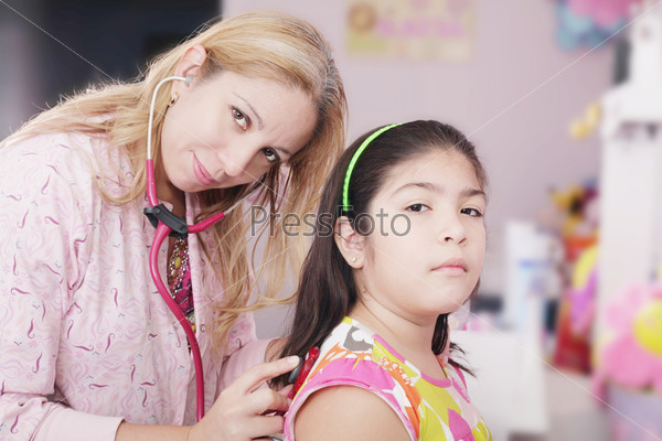 Pediatrician examining little girl with stethoscope