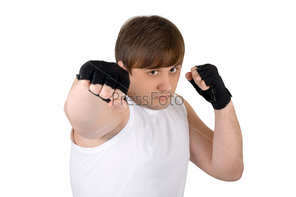 Young man throwing a punch. Isolated on white