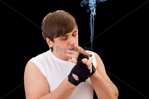 Young man sets fire to a cigar