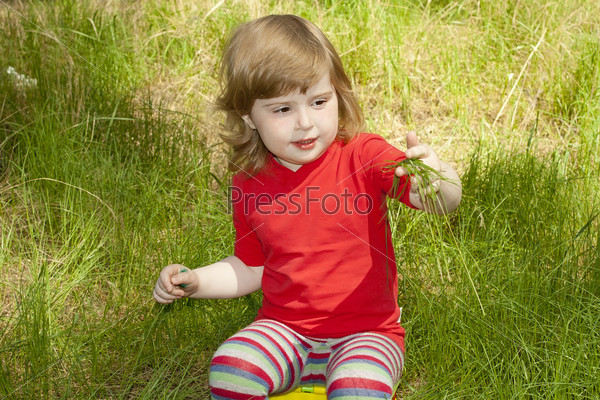 a little girl sitting on a chair in the grass