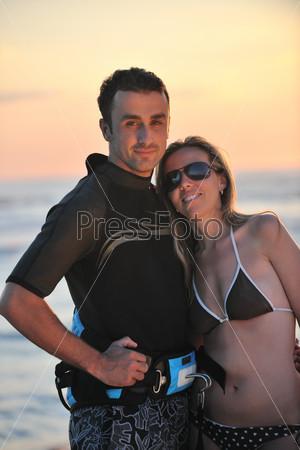 surf couple posing at beach on sunset