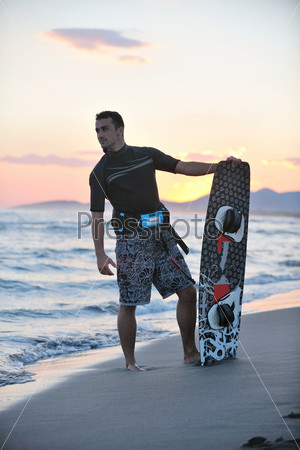 Portrait of a young  kitsurf  man at beach on sunset