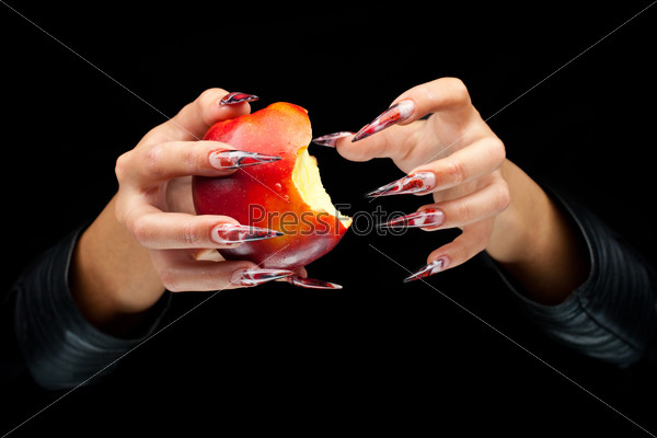 Bitten apple in woman hands with art nails