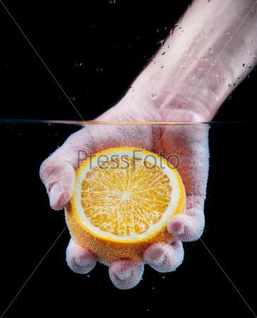 Orange in the hand under water