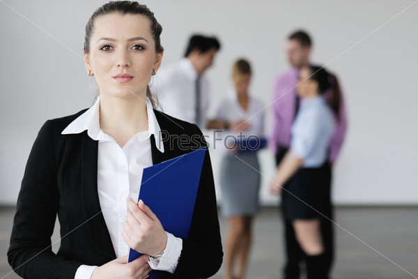 business woman standing with her staff in background
