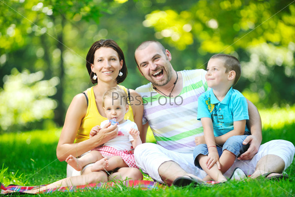 happy young couple with their children have fun at park