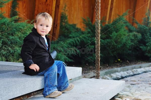 Красивый мальчик в пиджаке на открытом воздухе