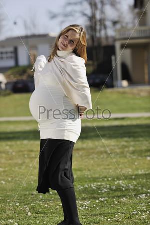 Счастливая молодая беременная женщина на открытом воздухе