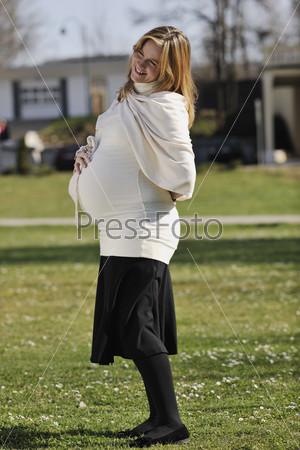 Счастливая молодая беременная женщина на открытом воздухе в солнечный день