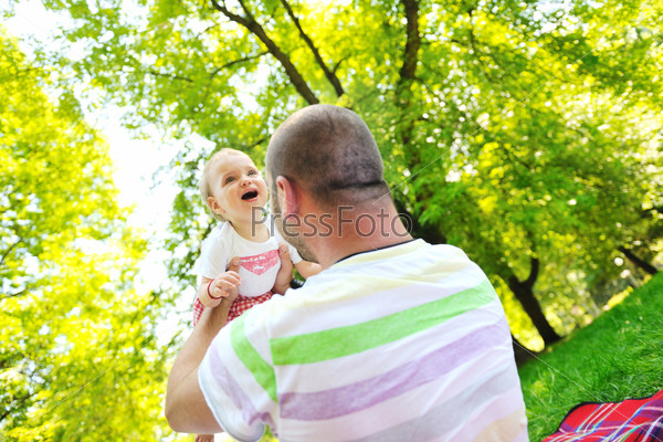 man and baby playing in park