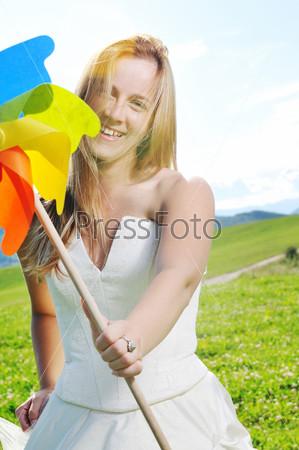 Счастливая молодая красивая невеста с вертушкой в руке на открытом воздухе