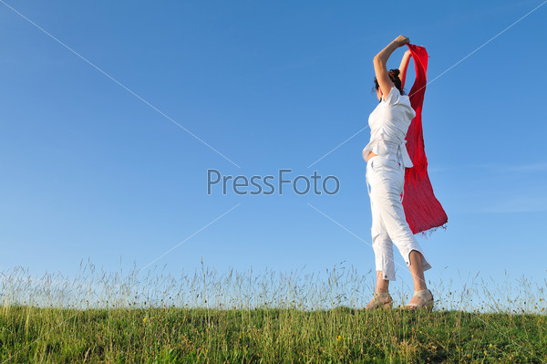 beautiful woman with red scarf on meadow