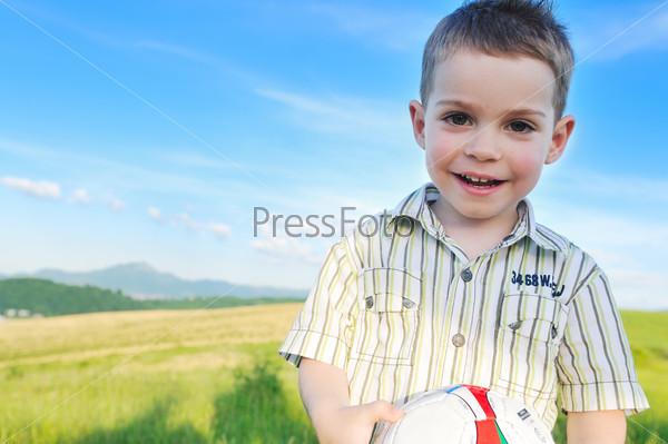 Портрет мальчика с мячом в руках на природе