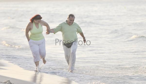 happy seniors couple  on beach