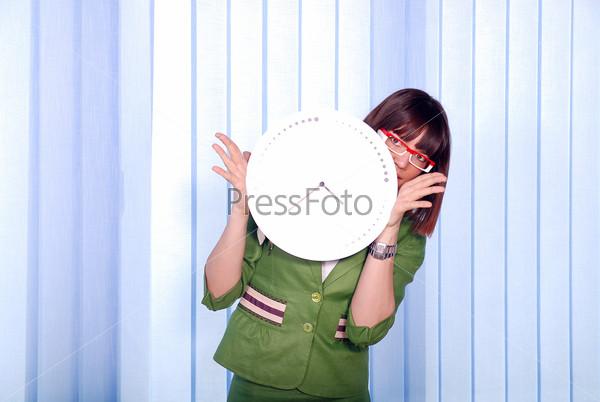 .a pretty business woman hiding behind a clock