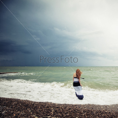The woman on the beach during a storm