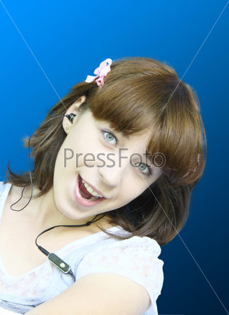 The young cheerful girl sings in ear-phones