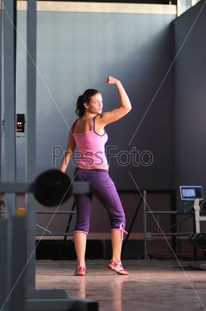young woman with strong arms rising hands in air