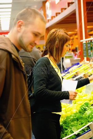 happy couple buying fruits in hypermarket
