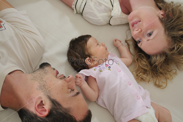 young family playing with cute little baby
