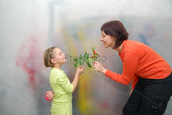 Girl giving mother flowers