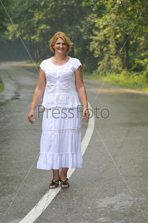 middle age woman walk on white line on road outdoor