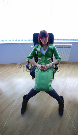 Businesswoman in green suit seating on office chair