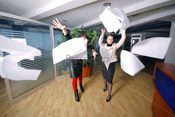 two businesswoman throw papers in office