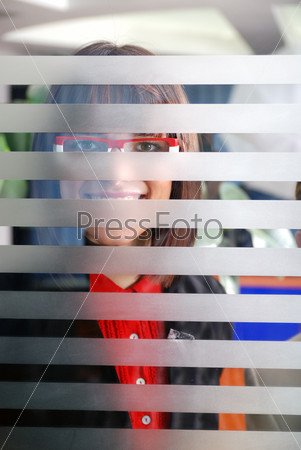 young businesswoman looking trought transparent wall