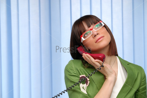 .businesswoman in green suit talking by cellphone