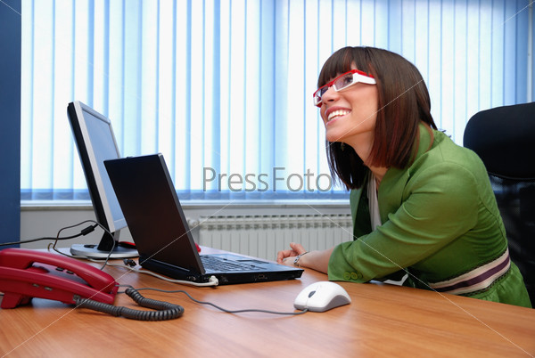 Smiling young businesswoman working on a laptop in the office.