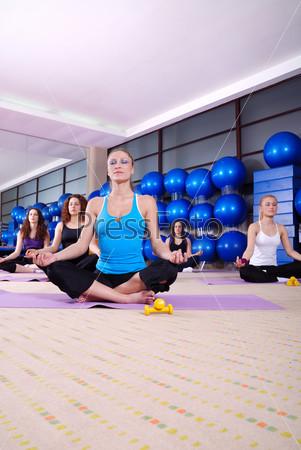 Beautiful girls meditating in fitness club
