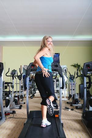 Молодая женщина на беговой дорожке в спортивном зале