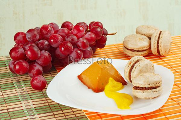 Кофе, макаруны, карамельный пудинг и виноград на столе
