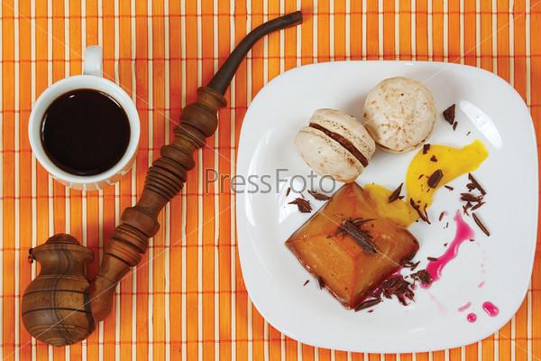 Кофе, макаруны, трубка, карамельный пудинг на столе