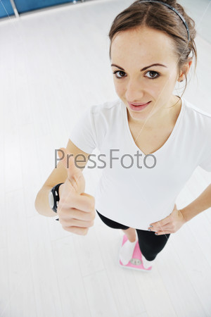 happy diet concept with young woman on pink scale