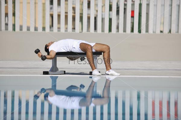Мужчина выполняет упражнения у бассейна