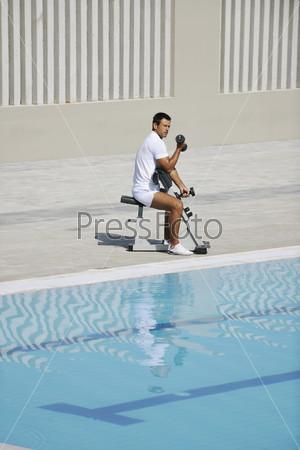 Молодой спортсмен выполняет упражнение с гантелями у бассейна