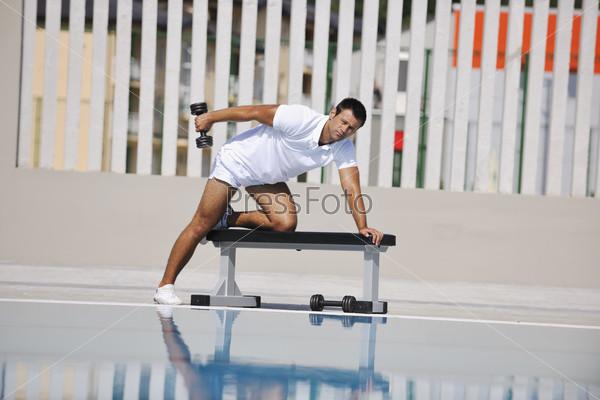 Молодой спортсмен выполняет упражнение с гантелью у бассейна