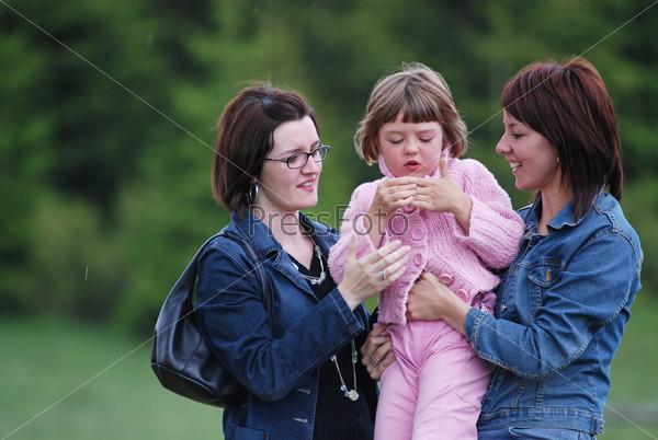 Две девушки с маленькой девочкой на открытом воздухе