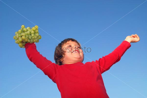 Девочка с виноградом на открытом воздухе