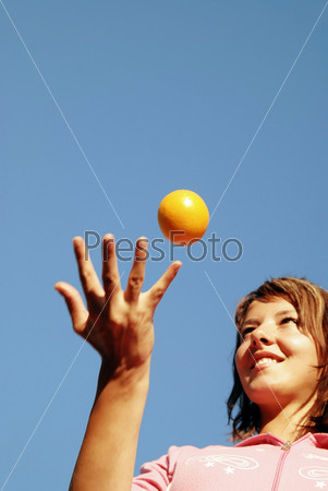 beautyful girl throwing orange in air
