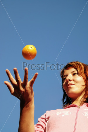 beautyful girl throwing orange in air