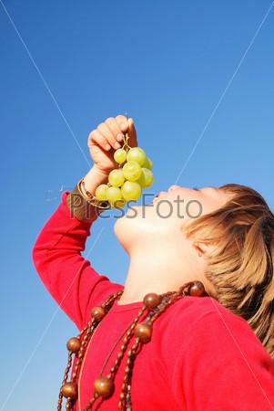 Девочка ест виноград на фоне голубого неба