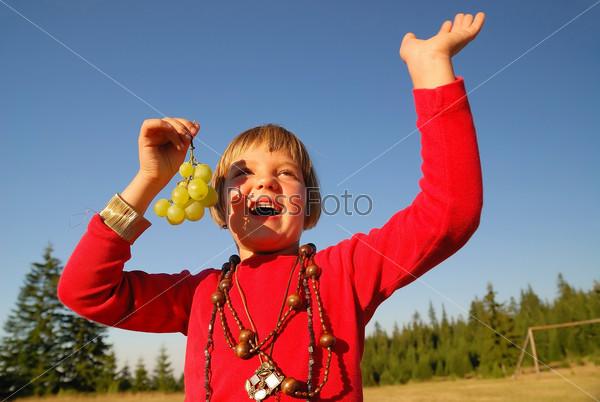Девочка с виноградом на природе