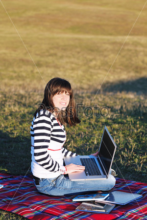 young teen girl work on laptop outdoor